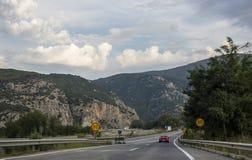 Εθνική οδός ενάντια στα βουνά και έναν νεφελώδη ουρανό Στοκ Φωτογραφίες