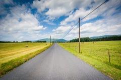 Εθνική οδός με τα απόμακρους βουνά και τους αγροτικούς τομείς στον αγροτικό Στοκ Εικόνες