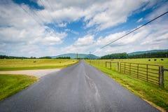 Εθνική οδός με τα απόμακρους βουνά και τους αγροτικούς τομείς στον αγροτικό Στοκ Φωτογραφίες