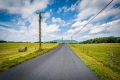 Εθνική οδός με τα απόμακρους βουνά και τους αγροτικούς τομείς στον αγροτικό Στοκ Εικόνα