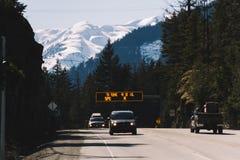 Εθνική οδός με τα αυτοκίνητα και τα χιονώδη βουνά στο υπόβαθρο Στοκ φωτογραφία με δικαίωμα ελεύθερης χρήσης