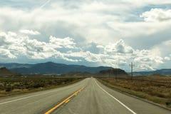 Εθνική οδός με τα σύννεφα και τα βουνά Στοκ Φωτογραφία