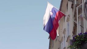 Εθνική σημαία της δημοκρατίας της Σλοβενίας ενάντια στον ήλιο και το μπλε ουρανό που κυματίζουν έξω από ένα διαμέρισμα Σε αργή κί απόθεμα βίντεο