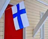 Εθνική φινλανδική σημαία πέρα από το σπίτι Στοκ Φωτογραφία