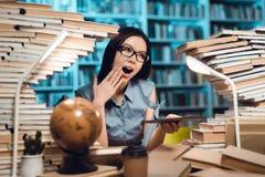 Εθνικό ασιατικό κορίτσι που περιβάλλεται από τα βιβλία στη βιβλιοθήκη τη νύχτα Ο σπουδαστής χρησιμοποιεί την ταμπλέτα στοκ εικόνες