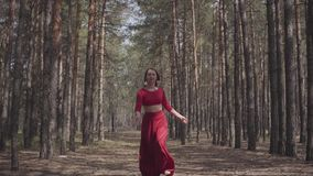 Ειδικευμένη χαριτωμένη γυναίκα στο κόκκινο φόρεμα που χορεύει στο δασικό τοπίο Όμορφος σύγχρονος χορευτής Χαριτωμένα τρεξίματα κο απόθεμα βίντεο