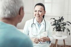 Ειδικευμένη χαριτωμένη νοσοκόμα που χαμογελά και που διοργανώνει τις διαβουλεύσεις στοκ εικόνες