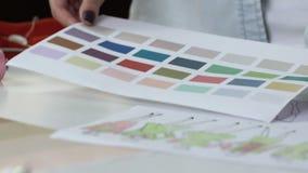 Ειδικευμένος γυναικείος σχεδιαστής που λαμβάνει την απόφαση για την παλέτα χρώματος για το ράψιμο της εξάρτησης απόθεμα βίντεο