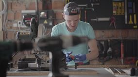 Ειδικευμένος ξυλουργός που κόβει ένα κομμάτι της λεπτομέρειας χαρτονιού στο εργαστήριο ξυλουργικής του, που χρησιμοποιεί ένα κυκλ απόθεμα βίντεο