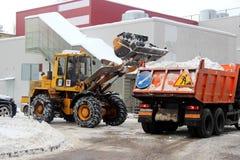 Ειδικός εξοπλισμός αφαίρεσης χιονιού υπηρεσιών πόλεων μετά από τις χιονοπτώσεις αστικές χρησιμότητες Το τρακτέρ φορτώνει το χιόνι στοκ φωτογραφία