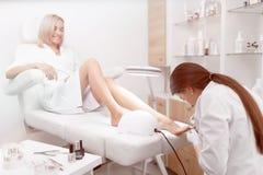 Ειδικός στην άσπρη καθαρίζοντας επιδερμίδα γύρω από τα καρφιά στα πόδια και po στοκ φωτογραφία με δικαίωμα ελεύθερης χρήσης