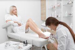 Ειδικός στην άσπρη καθαρίζοντας επιδερμίδα γύρω από τα καρφιά στα πόδια και τη στιλβωτική ουσία στοκ εικόνες