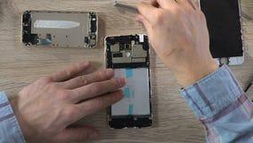 Ειδικός Smartphone που επισκευάζει τη συσκευή και που αλλάζει το μικροτσίπ, τεχνολογίες φιλμ μικρού μήκους