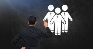Εικονίδια επιχειρηματιών στο σκοτεινό τοίχο με τον επιχειρηματία Στοκ Φωτογραφίες