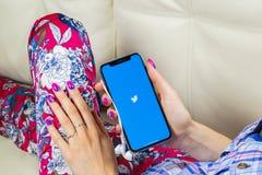 Εικονίδιο εφαρμογής πειραχτηριών στο iPhone Χ της Apple κινηματογράφηση σε πρώτο πλάνο οθόνης smartphone στα χέρια γυναικών App π Στοκ Εικόνες