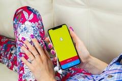 Εικονίδιο εφαρμογής Snapchat στο iPhone Χ της Apple κινηματογράφηση σε πρώτο πλάνο οθόνης smartphone στα χέρια γυναικών App Snapc Στοκ Φωτογραφία