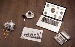 Εικονίδια γραφικών παραστάσεων διαγραμμάτων πιτών στην οθόνη lap-top με τα εξαρτήματα γραφείων Στοκ Φωτογραφίες