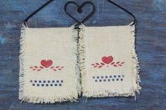 Εικονίδιο καρδιών αγάπης στην ένωση υφάσματος στην κρεμάστρα στο παλαιό ξύλινο υπόβαθρο Στοκ Φωτογραφίες