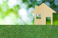 Εικονίδιο σπιτιών από ξύλινο στο υπόβαθρο φύσης σύστασης χλόης ως σύμβολο της υποθήκης Στοκ εικόνα με δικαίωμα ελεύθερης χρήσης