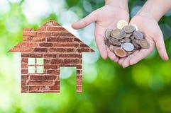 Εικονίδιο σπιτιών εκμετάλλευσης χεριών νομισμάτων στη φύση ως σύμβολο της υποθήκης, σπίτι ονείρου στο υπόβαθρο φύσης Στοκ φωτογραφία με δικαίωμα ελεύθερης χρήσης