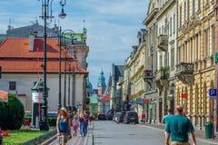 Εικονική παράσταση πόλης της παλαιών πόλης, των τουριστών και των πολιτών που περπατούν στην οδό Szpitalna Στοκ εικόνες με δικαίωμα ελεύθερης χρήσης