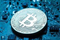 Εικονικό νόμισμα bitcoin σε ένα τυπωμένο υπόβαθρο πινάκων κυκλωμάτων Στοκ Εικόνες