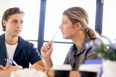Εικόνα δύο νέων επιχειρηματιών στην αρχή στοκ εικόνες