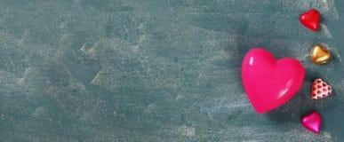 Εικόνα εμβλημάτων ιστοχώρου των ζωηρόχρωμων σοκολατών μορφής καρδιών στον ξύλινο πίνακα Έννοια εορτασμού ημέρας βαλεντίνου Στοκ Εικόνες