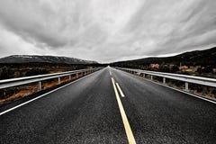 Εικόνα ενός ευρέος ανοικτού λιβαδιού και των βουνών με έναν στρωμένο δρόμο εθνικών οδών που τεντώνει έξω όσο το μάτι μπορεί να δε Στοκ εικόνα με δικαίωμα ελεύθερης χρήσης