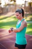Εικόνα ενός θηλυκού αθλητή που ρυθμίζει το όργανο ελέγχου ποσοστού καρδιών της Στοκ Φωτογραφίες