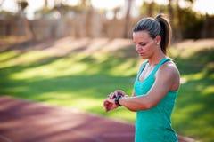 Εικόνα ενός θηλυκού αθλητή που ρυθμίζει το όργανο ελέγχου ποσοστού καρδιών της Στοκ φωτογραφία με δικαίωμα ελεύθερης χρήσης