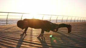 Εικόνα ενός νέου αθλητικού τύπου που κάνει την ώθηση UPS υπαίθρια στο ξύλινο froor στο μέτωπο η θάλασσα ή ο ωκεανός Ικανότητα και φιλμ μικρού μήκους