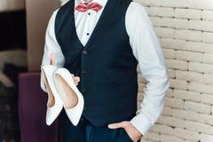 Εικόνα ενός νεόνυμφου που κρατά τα νυφικά παπούτσια στοκ φωτογραφία