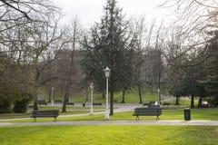 Εικόνα ενός πάρκου με τους πάγκους, τη χλόη και τα δέντρα στοκ εικόνα με δικαίωμα ελεύθερης χρήσης