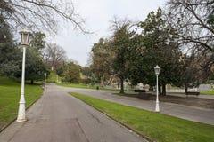 Εικόνα ενός πάρκου με τους πάγκους, τη χλόη και τα δέντρα στοκ φωτογραφία