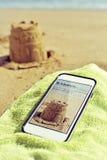 Εικόνα ενός sandcastle και ενός σπασίματος Μαρτίου κειμένων σε ένα smartphone Στοκ Εικόνα