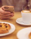 Εικόνα λεπτομέρειας του unrecognisable καφέ κατανάλωσης ατόμων και κράτημα του έξυπνου τηλεφώνου ενώ έχοντας το πρόγευμα στο εστι Στοκ Εικόνα