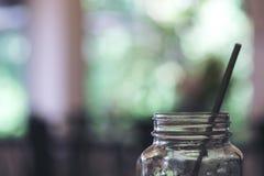 Εικόνα κινηματογραφήσεων σε πρώτο πλάνο ενός μπουκαλιού και ενός αχύρου γυαλιού με την πράσινη φύση θαμπάδων στοκ εικόνες