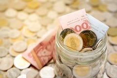 Εικόνα κινηματογραφήσεων σε πρώτο πλάνο ενός συνόλου βάζων γυαλιού των νέων ταϊλανδικών τραπεζογραμματίων και των νομισμάτων μπατ στοκ φωτογραφία