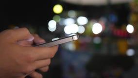 Εικόνα κινηματογραφήσεων σε πρώτο πλάνο το των χεριών παιδιών ` s που χρησιμοποιούν ένα smartphone τη νύχτα σε μια οδό αγορών πόλ απόθεμα βίντεο
