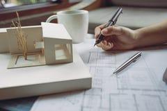 Εικόνα κινηματογραφήσεων σε πρώτο πλάνο των αρχιτεκτόνων που σύρουν το έγγραφο σχεδίων καταστημάτων με το πρότυπο αρχιτεκτονικής Στοκ Φωτογραφία