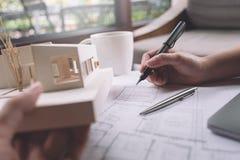 Εικόνα κινηματογραφήσεων σε πρώτο πλάνο των αρχιτεκτόνων που σύρουν το έγγραφο σχεδίων καταστημάτων με το πρότυπο αρχιτεκτονικής Στοκ Εικόνες