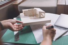 Εικόνα κινηματογραφήσεων σε πρώτο πλάνο των αρχιτεκτόνων που σύρουν το έγγραφο σχεδίων καταστημάτων με το πρότυπο αρχιτεκτονικής Στοκ φωτογραφία με δικαίωμα ελεύθερης χρήσης