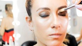 Εικόνα κινηματογραφήσεων σε πρώτο πλάνο των ματιών προτύπων ζωγραφικής καλλιτεχνών makeup με τη βούρτσα στοκ φωτογραφίες