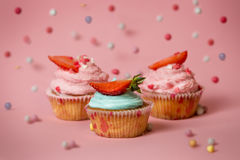 Εικόνα κινηματογραφήσεων σε πρώτο πλάνο τριών ζωηρόχρωμων cupcakes με τις φράουλες στο pi Στοκ εικόνες με δικαίωμα ελεύθερης χρήσης