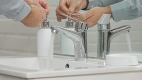 Εικόνα με το άτομο στο λουτρό που πλένει τα χέρια του στοκ εικόνα