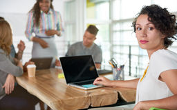 Εικόνα μιας επιτυχούς περιστασιακής επιχειρησιακής γυναίκας που χρησιμοποιεί το lap-top κατά τη διάρκεια της συνεδρίασης Στοκ Φωτογραφία