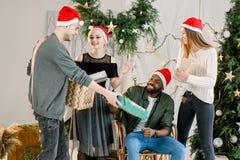 Εικόνα που παρουσιάζει ομάδα φίλων που γιορτάζουν τα Χριστούγεννα στο σπίτι και που ανταλλάσσουν τα δώρα Χριστουγέννων στοκ φωτογραφίες