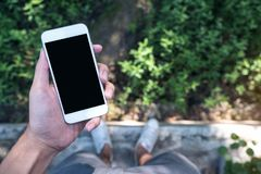 Εικόνα προτύπων ενός χεριού ατόμων ` s που κρατά το άσπρο κινητό τηλέφωνο με την κενή μαύρη οθόνη στεμένος στο τσιμεντένιο πάτωμα Στοκ Εικόνες