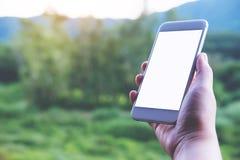 Εικόνα προτύπων ενός χεριού που κρατά και που παρουσιάζει άσπρο έξυπνο τηλέφωνο με την κενή οθόνη σε υπαίθριο Στοκ φωτογραφία με δικαίωμα ελεύθερης χρήσης